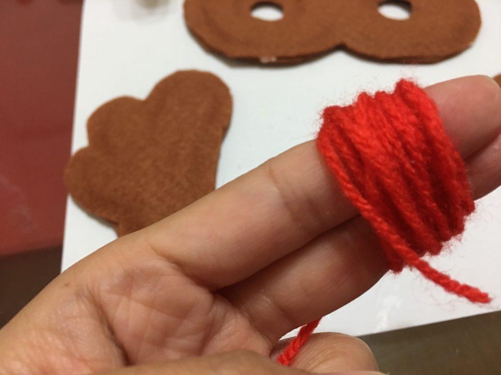指に巻きつけた赤い毛糸