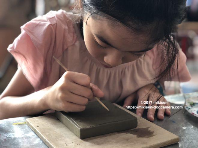 コースター彫刻をする子供